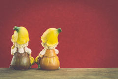 Two ceramic doll sit on wood Stock Image