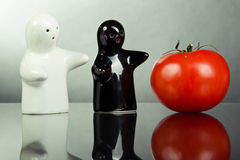 Two ceramic figures indicate tomato. Two ceramic figurines, point in the direction of red tomatoes Stock Photography