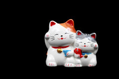 Two ceramic lucky cats for decoration isolated on black Royalty Free Stock Photography