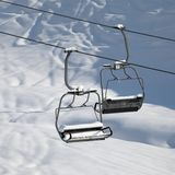 Two chair-lift with snowdrift in sun morning. Close-up view. Stock Photos