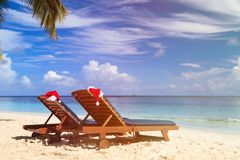 Two chair lounges with red Santa hats on tropical Stock Photos