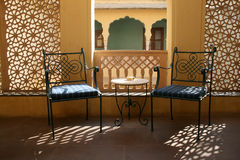 Two chairs. Two iron chairs on a terrace in an indian palace with sunlight playing through the filigree walls Royalty Free Stock Images