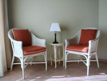 Two Chairs. Two wicker chairs and a table and lamp Royalty Free Stock Photography