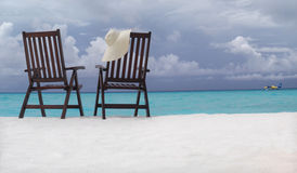 Two chairs on the beach. With hat Royalty Free Stock Images