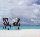 Two chairs on the beach. With hat Royalty Free Stock Photography