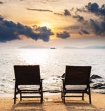 Two chairs on the beach in sunset, couple summer holiday vacation concept Royalty Free Stock Photo