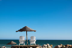 Two Chairs at the Beach. Two chairs and umbrella at the beach. Lighthouse Island, Algarve, Portugal stock photography