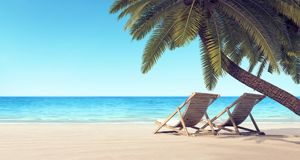 Two chairs on the beach under palm tree summer background