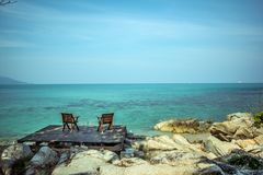 Two chairs on the beach in the wooden board Stock Images