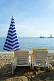 Two chairs and closed umbrella on  the beach Royalty Free Stock Image
