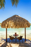 Two chairs and coffee table under a thatched parasol on a sand b Stock Photos