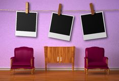 Two chairs with console and hanging frames Royalty Free Stock Photography