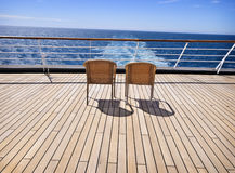 Two Chairs on Deck. Two woven chairs on the wooden deck of a cruise ship waiting for two people to sit down, relax, and watch the beautiful blue water and sky royalty free stock images