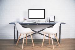 Two chairs at desk. Two chairs next to designer desk with blank white computer screen and other items on wooden floor and brick background. Mock up Stock Photo