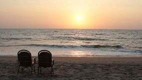 Two chairs near coastline at sunset stock video footage