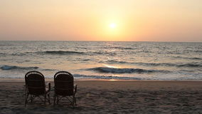 Two chairs near coastline at sunset time stock video footage