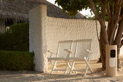 Two chairs near spa bungalow center on tropical island in Maldives at exotic resort on the white sand beach Royalty Free Stock Photos