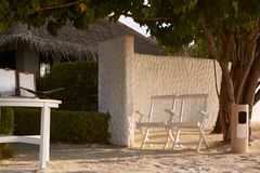 Two chairs and table with list of services near spa center bungalow entrance on tropical island in Maldives at exotic Stock Photos