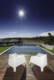 Two chairs with near swimming pool and wooden deck Stock Photo