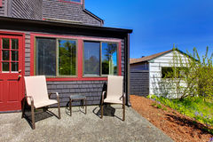 Two chairs next to red door and small black house. Royalty Free Stock Image
