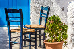 Two chairs outside a Greek home, in traditional blue and white color scheme Royalty Free Stock Images