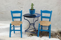 Two chairs outside a Greek restaurant. In te traditional blue and white color scheme royalty free stock photography
