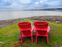 Two chairs overlooking ocean shore Royalty Free Stock Images