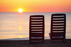 Two chairs stand on beach in evening Stock Photography