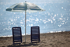 Two chairs stand on beach near sea Stock Images