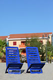 Two chairs stand under sun on beach near cottages royalty free stock photography