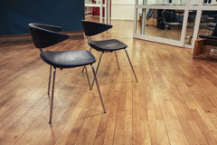 Two chairs standing on a parquet floor Royalty Free Stock Images