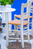 Two chairs on a street of typical greek traditional village on Mykonos Island, Greece, Europe Stock Images