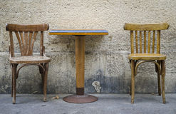 Two chairs and a table. Old chairs and table on sidewalk in Paris Stock Image