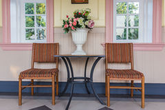 Two chairs and table with bouquet of flowers in vase on a patio Royalty Free Stock Image