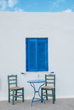 Two chairs and a table in front of a white greek house Stock Photos