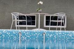 Two chairs and a table by the pool Stock Image