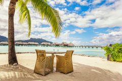 Two chairs and table on a sand beach with a view on the lagoon a Royalty Free Stock Photo