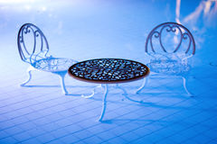 Two chairs and a table stand in the pool Royalty Free Stock Image