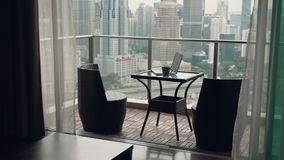 Two chairs at terrace. Teo chairs and a table with cup of coffee and open laptop at terrace with beautiful view over the city. Luxury apartment balcony and stock video footage