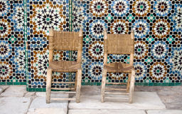 Two chairs on tiles background. Two chairs and zellij tiles, Ben Youssef Medersa, Marrakesh Royalty Free Stock Images