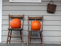 Two chairs and two fall pumpkins Stock Image