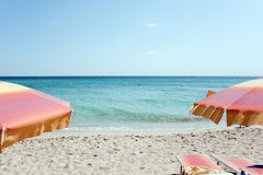 Two chairs and two umbrellas on the beach Royalty Free Stock Photos