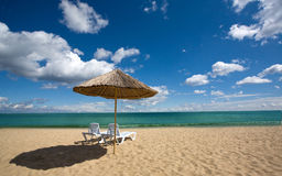 Two chairs and umbrella on the beach Royalty Free Stock Images