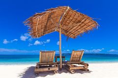 Two chairs and umbrella on beach stock photo