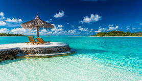 Two chairs and umbrella on a jetty on a tropical island royalty free stock photos