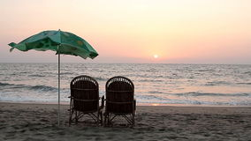 Two chairs and umbrella near coastline at sunset time stock video