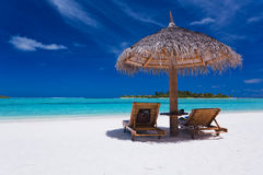 Two chairs and umbrella on stunning beach. Two chairs and umbrella on stunning tropical beach Stock Photography