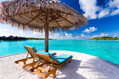 Two chairs and umbrella on tropical beach royalty free stock photos
