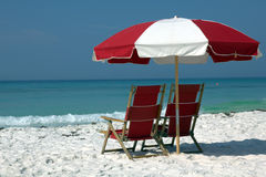 Two chairs and umbrella on white sand beach Stock Images