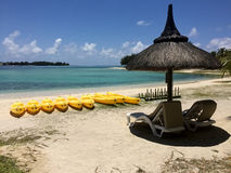 Two chairs and umbrella with yellow canoes at the beach. Blue sky and blue ocean water Royalty Free Stock Images
